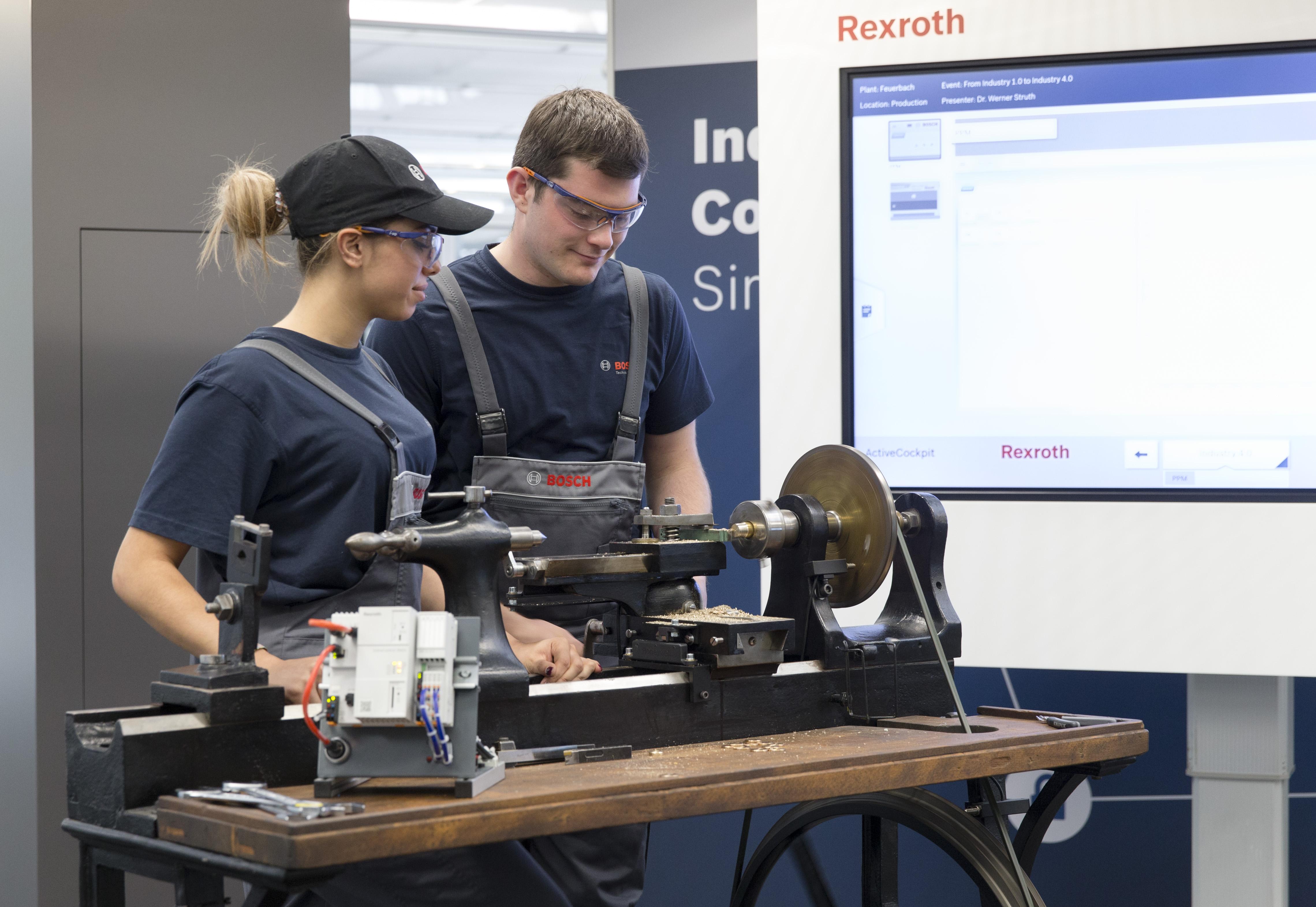 Dvaja učni spoločnosti Bosch - Sina Rohloff a Felix Meeh vyrábajú kovové diely na historickom sústruhu z roku 1887