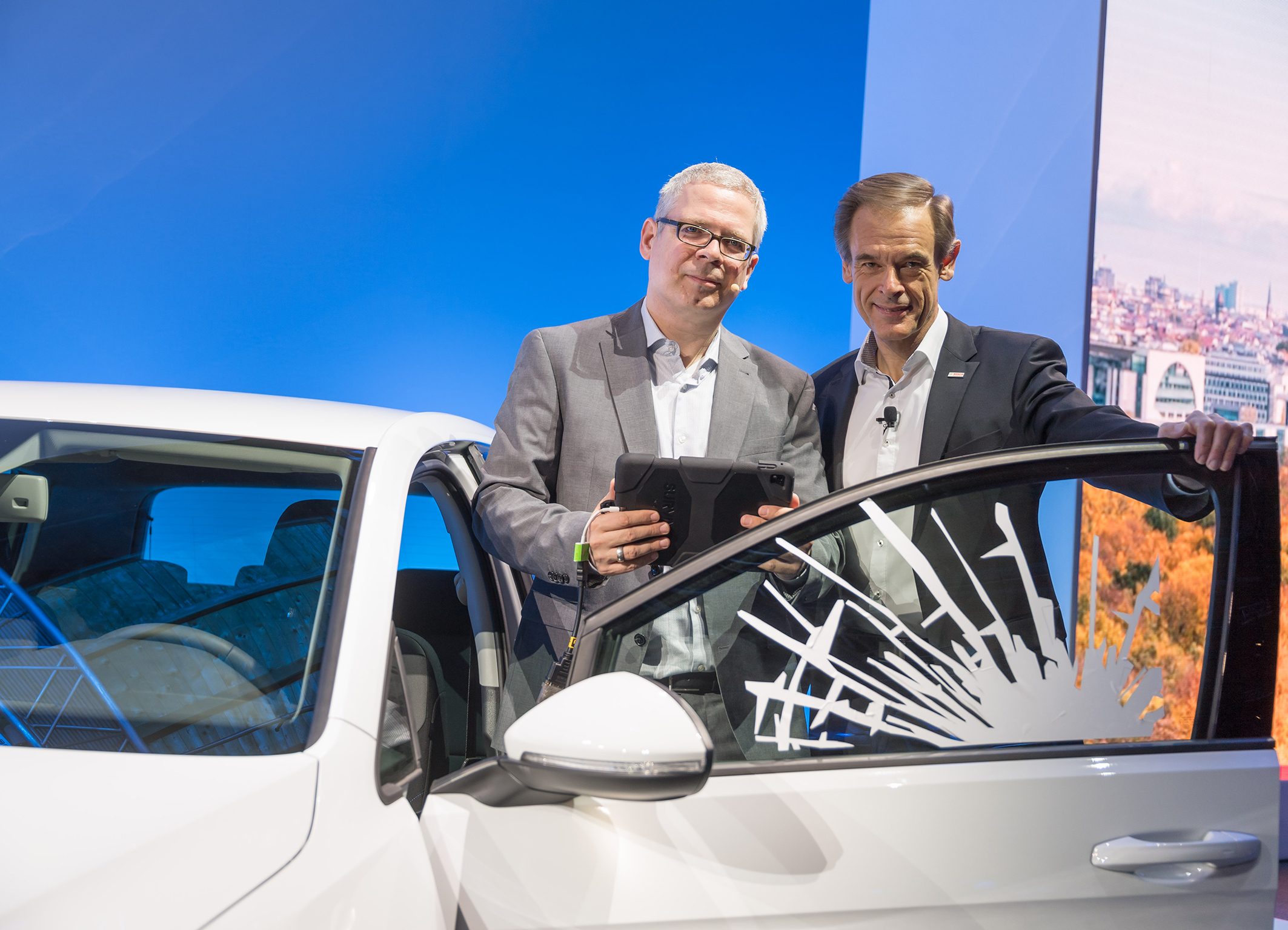 Bosch CEO Dr. Volkmar Denner and MC Dirk Slama demonstrate the connected repair shop as part of the opening address at Bosch Connected World 2017